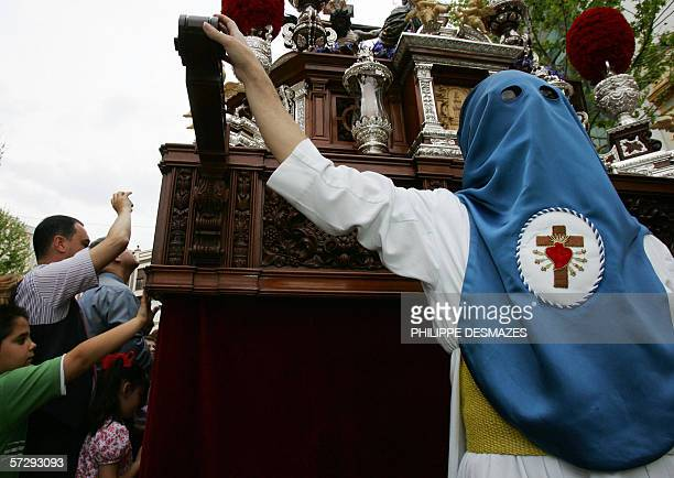 """Penitent walks in the brotherhood parade during the procession """"Nuestra Senora de la Hiniesta"""" for the first day of the famous the holy week in..."""