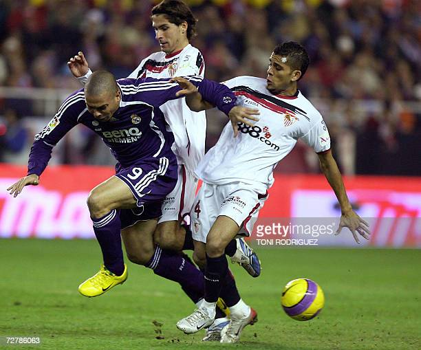 Real Madrid's Brazilian forward Ronaldo is tackled by Sevilla's Julie Escude and Daniel Alves during a Spanish league football match at the Sanchez...