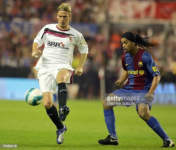 Sevilla's Danish Christian Poulsen vies with Barcelona's Brazilian Ronaldinho during a Spanish league football match at the Sanchez Pizjuan stadium...