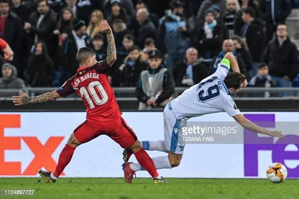 Sevilla's Argentine midfielder Ever Banega tackles Lazio's Bosnian midfielder Senad Lulic during the UEFA Europa League round of 16 first leg...