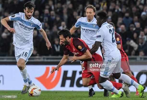 Sevilla's Argentine midfielder Franco Vazquez is tackled by Lazio's Ecuadorian forward Felipe Caicedo as Lazio's Italian midfielder Marco Parolo...