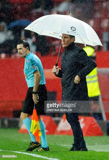 Sevilla's Argentinian coach Eduardo Berizzo holds an umbrella as he stands on the sideline during the Spanish league football match Sevilla FC vs...