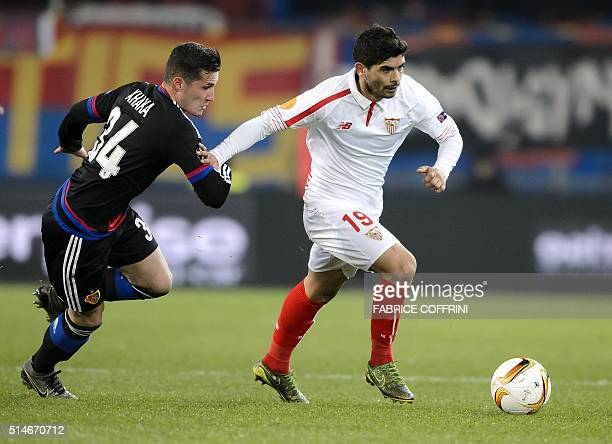 Sevilla's Argentinian midfielder Ever Banega and Basel's Swiss midfielder Taulant Xhaka vies during the UEFA Europa League round of 16 first leg...