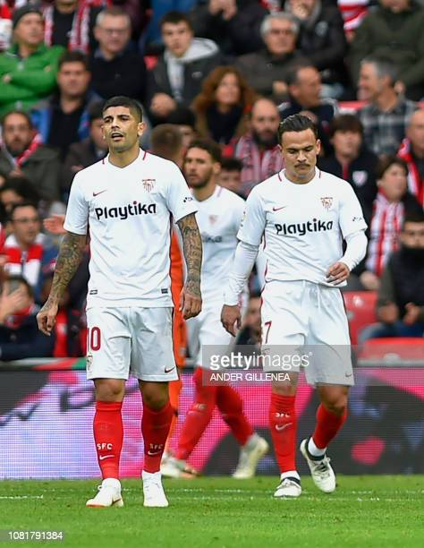Sevilla's Argentinian midfielder Ever Banega and Spanish midfielder Roque Mesa react during the Spanish League football match between Athletic Club...