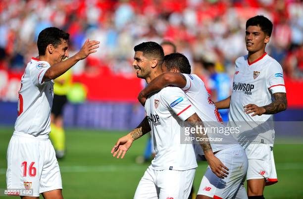 Sevilla's Argentinian midfielder Ever Banega celebrates with teammates after scoring a goal during the Spanish league football match Sevilla FC vs...