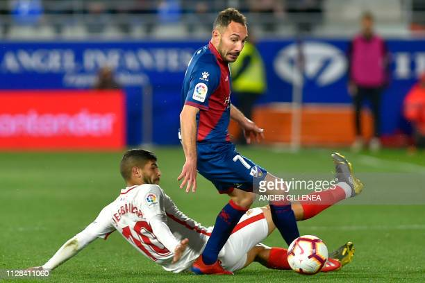 Sevilla's Argentinian midfielder Ever Banega challenges Huesca's Spanish midfielder David Ferreiro during the Spanish league football match between...