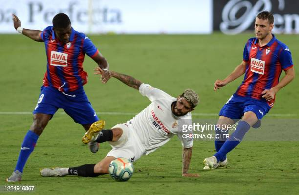 Sevilla's Argentinian midfielder Ever Banega fights for the ball with Eibar's Senegalese midfielder Pape Diop during the Spanish League football...