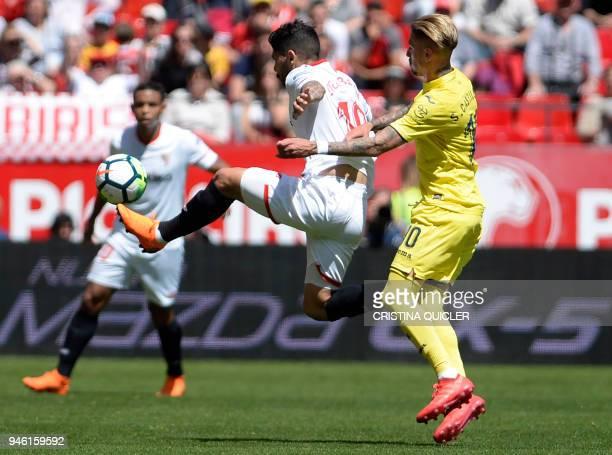 Sevilla's Argentinian midfielder Ever Banega jumps for the ball beside Villarreal's Spanish midfielder Samuel Castillejo Azuaga during the Spanish...