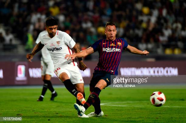Sevilla's Argentinian midfielder Ever Banega passes the ball next to Barcelona's Brazilian midfielder Arthur during the Spanish Super Cup final...