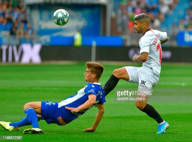 Sevilla's Argentinian midfielder Ever Banega vies with Alaves' Spanish midfielder Pere Pons during the Spanish league football match Deportivo Alaves...