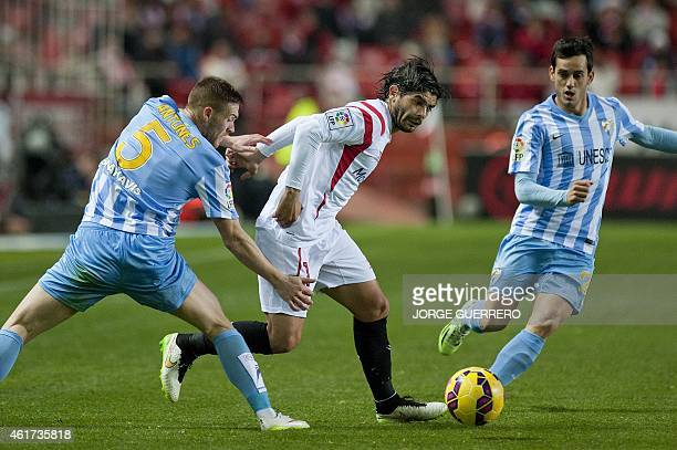 Sevilla's Argentinian midfielder Ever Banega vies with Malaga's Portuguese defender Vitorino Gabriel Antunes and forward Juanmi during the Spanish...