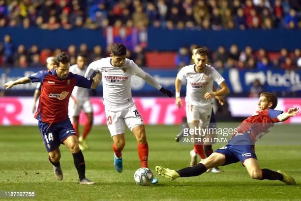 Sevilla's Argentinian midfielder Ever Banega vies with Osasuna's Spanish midfielder Ruben Garcia and Osasuna's Serbian midfielder Darko Brasanac...