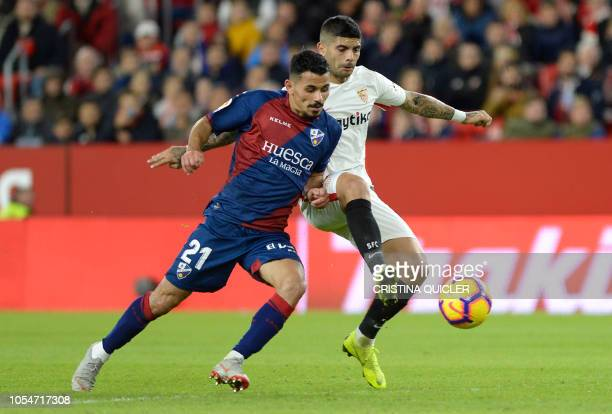 Sevilla's Argentinian midfielder Ever Banega vies with SD Huesca's Turkish midfielder Serdar Gurler during the Spanish league football match between...