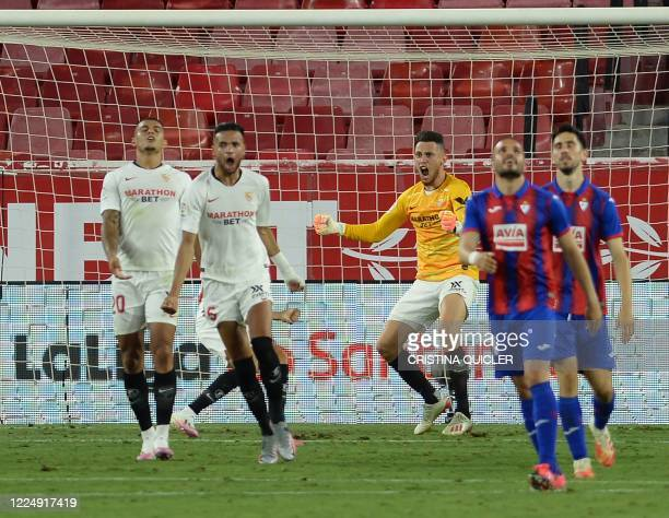 Sevilla's Argentinian midfielder Lucas Ocampos celebrates stopping a shot after replacing teammate Czech goalkeeper Tomas Vaclik during the Spanish...