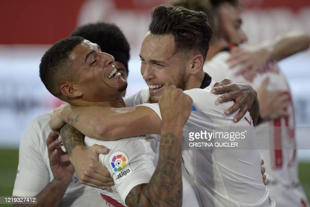 Sevilla's Argentinian midfielder Lucas Ocampos celebrates with teammates after scoring a goal during the Spanish League football match between...