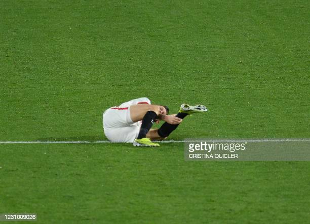 Sevilla's Argentinian midfielder Lucas Ocampos gestures in pain during the Spanish league football match between Sevilla FC and Getafe CF at the...