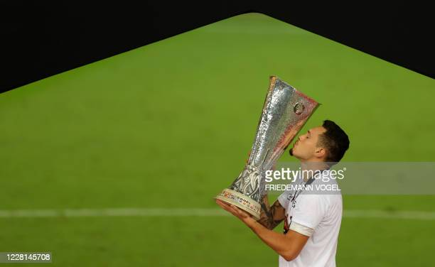 Sevilla's Argentinian midfielder Lucas Ocampos kisses the trophy after the UEFA Europa League final football match Sevilla v Inter Milan on August...