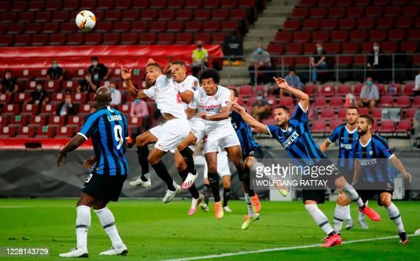Sevilla's Brazilian midfielder Fernando , Sevilla's French defender Jules Kounde and Inter Milan's Italian defender Danilo D'Ambrosio jump for the...