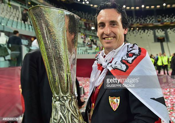 Sevilla's coach Unai Emery poses with the trophy after winning the UEFA Europa league final football match between Benfica and Sevilla on May 14 2014...