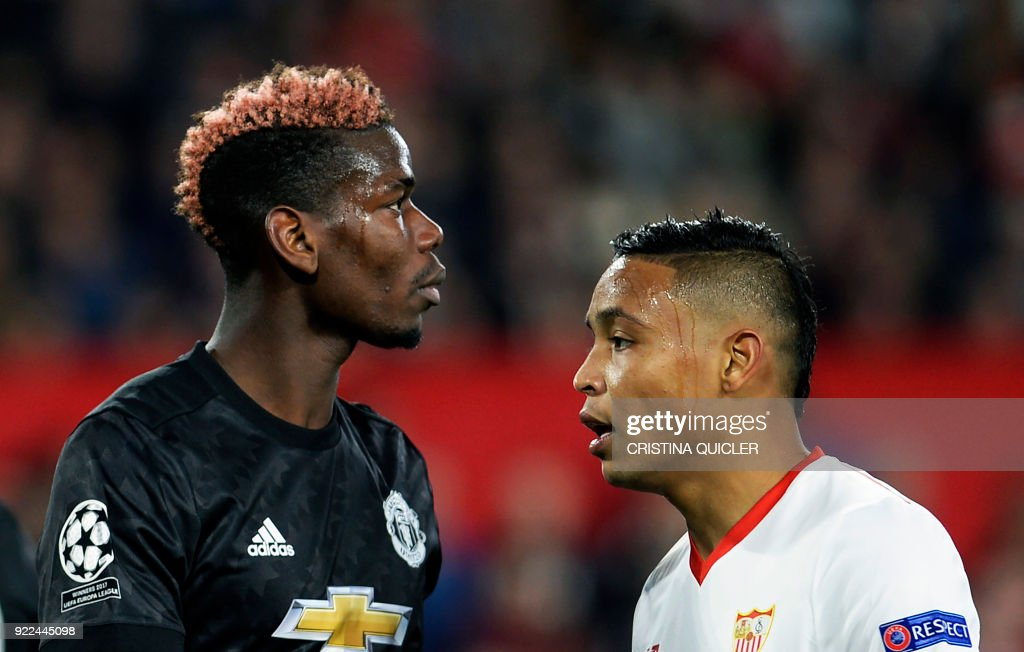 Sevilla's Colombian forward Luis Muriel (R) walks next to Manchester United's French midfielder Paul Pogba (L) during the UEFA Champions League round of 16 first leg football match Sevilla FC against Manchester United at the Ramon Sanchez Pizjuan stadium in Sevilla on February 21, 2018. / AFP PHOTO / Cristina Quicler