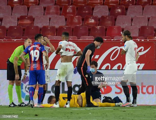 Sevilla's Czech goalkeeper Tomas Vaclik lays on the field after resulting injured during the Spanish League football match between Sevilla FC and SD...