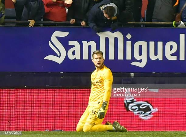 Sevilla's Czech goalkeeper Tomas Vaclik reacts kneeling to Osasuna's goal during the Spanish league football match between CA Osasuna and Sevilla FC...