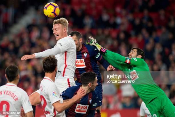 Sevilla's Danish defender Simon Kjaer jumps for the ball in front of Eibar's Spanish goalkeeper Asier Riesgo during the Spanish league football match...