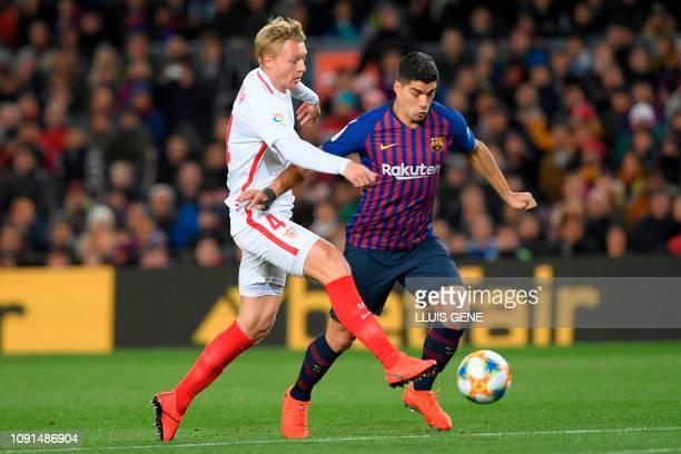 Sevilla's Danish defender Simon Kjaer vies for the ball with Barcelona's Uruguayan forward Luis Suarez during the Spanish Copa del Rey quarterfinal...