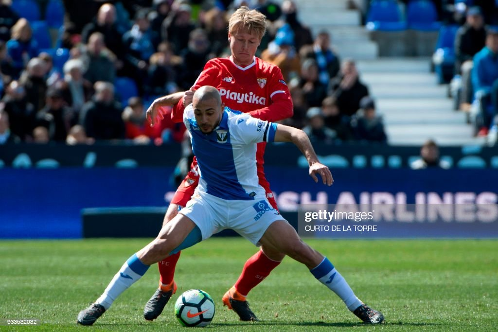 Sevilla's Danish defender Simon Kjaer (up) vies with Leganes' Moroccan forward Nordin Amrabat (front) during the Spanish League football match between Club Deportivo Leganes SAD and Sevilla FC at the Estadio Municipal Butarque in Leganes on March 18, 2018. / AFP PHOTO / CURTO DE LA TORRE / The erroneous mention[s] appearing in the metadata of this photo by CURTO DE LA TORRE has been modified in AFP systems in the following manner: [Leganes' Moroccan forward Nordin Amrabat] instead of [Leganes' Moroccan forward Nabil El Zhar]. Please immediately remove the erroneous mention[s] from all your online services and delete it (them) from your servers. If you have been authorized by AFP to distribute it (them) to third parties, please ensure that the same actions are carried out by them. Failure to promptly comply with these instructions will entail liability on your part for any continued or post notification usage. Therefore we thank you very much for all your attention and prompt action. We are sorry for the inconvenience this notification may cause and remain at your disposal for any further information you may require.