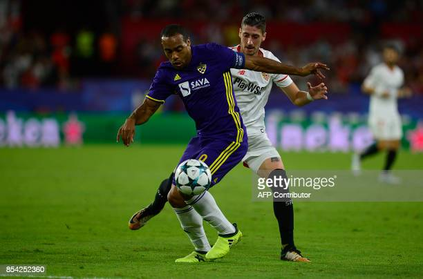 Sevilla's defender Sergio Escudero vies for the ball with Maribor's French defender Jean Claude Billong during the UEFA Champions League Group E...