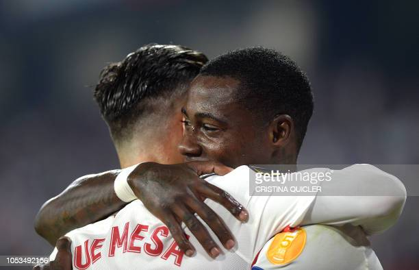 Sevilla's Dutch midfielder Quincy Promes celebrates with Sevilla's Spanish midfielder Roque Mesa after scoring a goal during the Europa League...