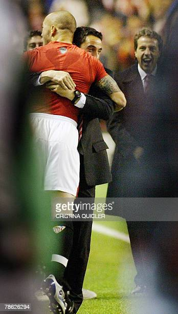 Sevilla's Ernesto Javier Chevanton of Uruguay hugs his coach Manolo Jimenez after scoring against Racing during a Spanish league football match at...