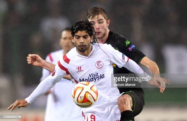 Sevilla's Ever Banega and Moenchengladbach's Christoph Kramer vie for the ball during the Europa League Round of 32 soccer match Borussia...