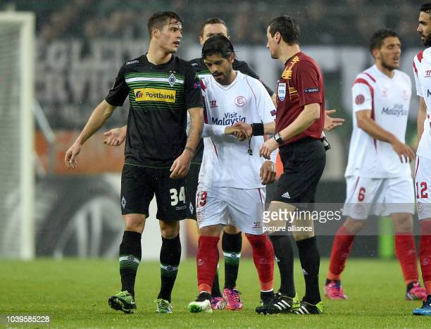Sevilla's Ever Banega and referee Marijo Strahonja shake hands as Moenchengladbach's Granit Xhaka argues during the Europa League Round of 32 soccer...