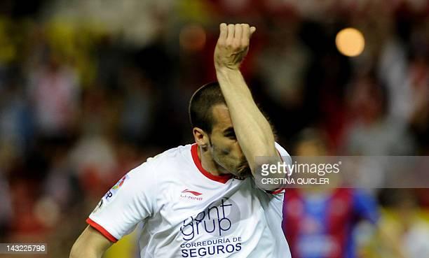 Sevilla's forward Alvaro Negredo kisses his tattoo as he celebrates after scoring during a Spanish League football match against Levante on April 21...