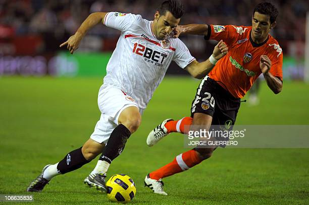 Sevilla's forward Alvaro Negredo vies for the ball with Valencia's Portuguese defender Ricardo Costa during their Liga football match Sevilla vs...