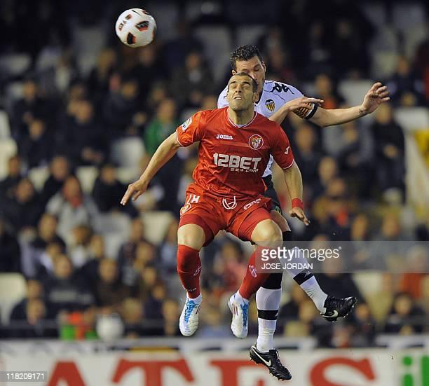 Sevilla's forward Alvaro Negredo vies for the ball with Valencia's defender David Navarro during the Spanish league football match Valencia CF vs...