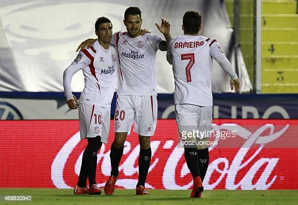 Sevilla's forward Jose Antonio Reyes celebrates his goal with teammates Sevilla's midfielder Vitolo and Sevilla's French forward Kevin Gameiro during...