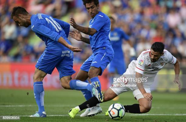 Sevilla's forward Nolito vies with Getafe's defender Juan Cala and Getafe's Uruguayan defender Damian Suarez during the Spanish league football match...