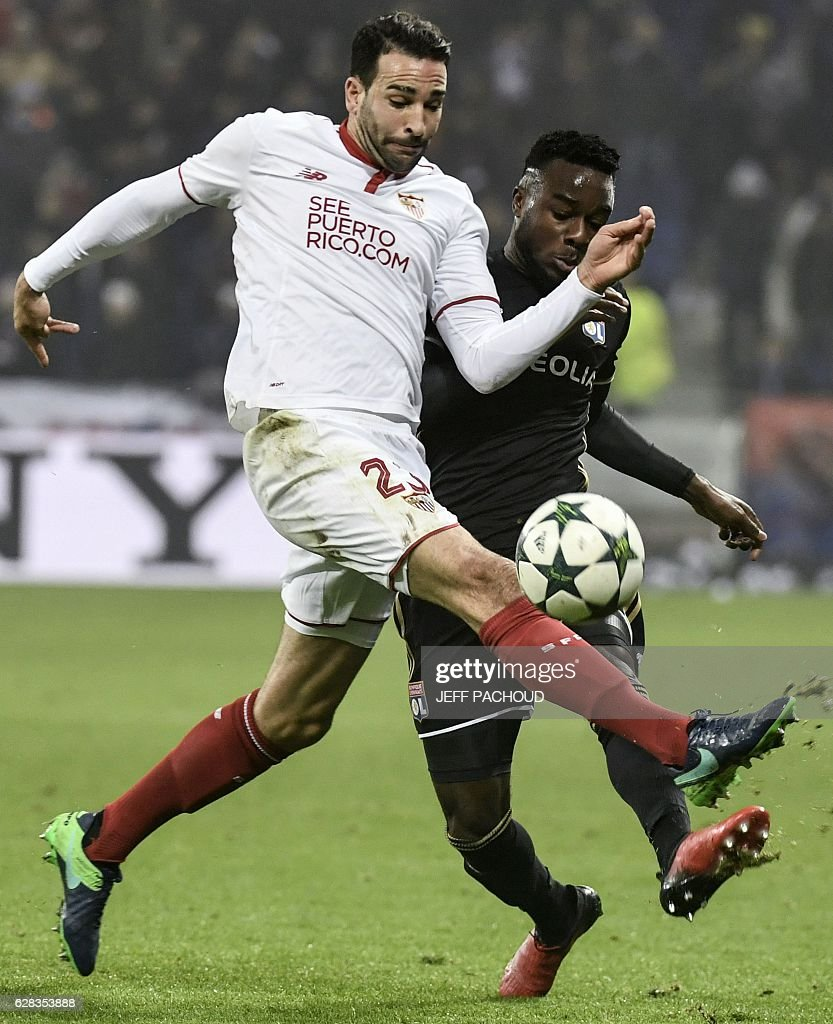 Sevilla's French defender Adil Rami (L) vies with Lyon's French forward Maxwel Cornet (R) during the UEFA Champions League Group H football match between Olympique Lyonnais (OL) and FC Sevilla at the Parc Olympique Lyonnais in Décines-Charpieu near Lyon, southeastern France, on December 7, 2016. / AFP / JEFF