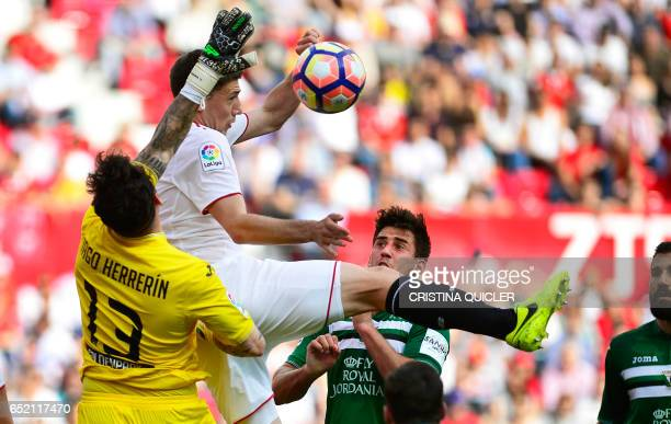 Sevilla's French defender Clement Lenglet jumps for the ball with Leganes' goalkeeper Iago Herrerin during the Spanish league football match Sevilla...