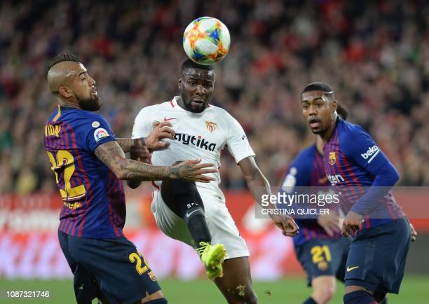 Sevilla's French defender Ibrahim Amadou vies with Barcelona's Chilean midfielder Arturo Vidal and Barcelona's Brazilian midfielder Malcom during the...