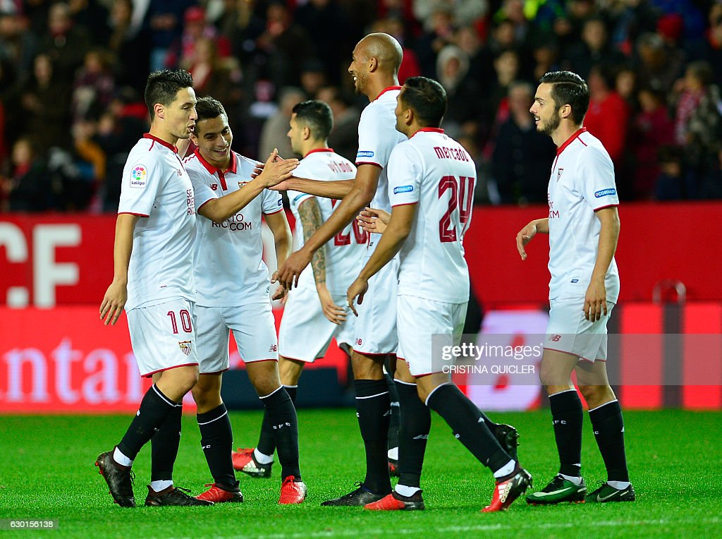 Sevilla's French forward Wissam Ben Yedder (2L) celebrates a goal with teammates during the Spanish league football match Sevilla FC vs Malaga CF at the Ramon Sanchez Pizjuan stadium in Sevilla on December 17, 2016. / AFP / CRISTINA