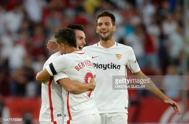 Sevilla's French forward Wissam Ben Yedder celebrates after scoring a goal with Sevilla's Spanish midfielder Pablo Sarabia and Sevilla's Italian...