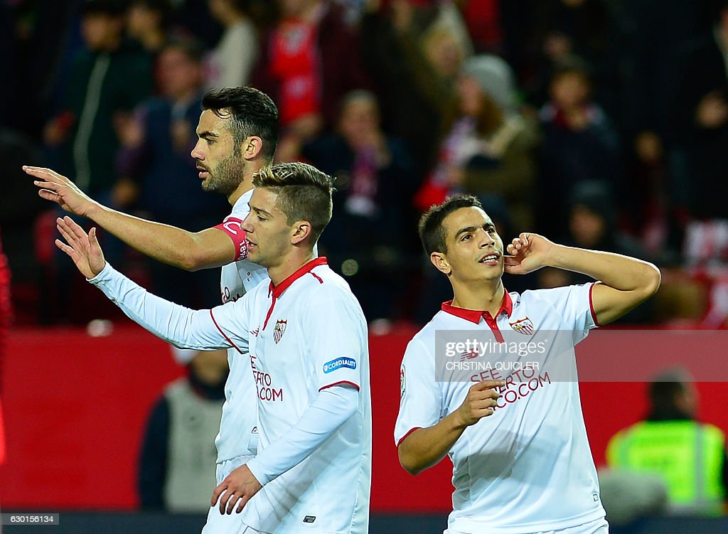 Sevilla's French forward Wissam Ben Yedder (R) celebrates after scoring a goal during the Spanish league football match Sevilla FC vs Malaga CF at the Ramon Sanchez Pizjuan stadium in Sevilla on December 17, 2016. / AFP / CRISTINA