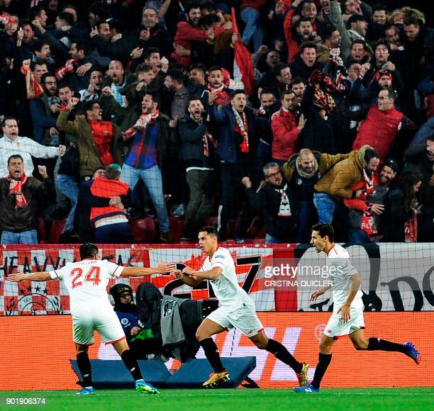 Sevilla's French forward Wissam Ben Yedder celebrates with Sevilla's forward Nolito and Sevilla's midfielder Jesus Navas after scoring a goal during...