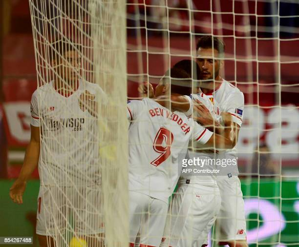 Sevilla's French forward Wissam Ben Yedder celebrates with teammates after scoring during the UEFA Champions League Group E football match Sevilla FC...