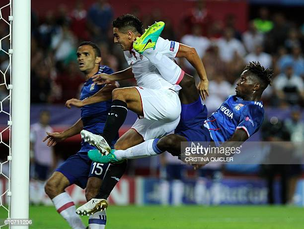 Sevilla's French forward Wissam Ben Yedder scores a goal beside Lyon's defender YangaMbiwa and Lyon's defender Jeremy Morel during the UEFA Champions...