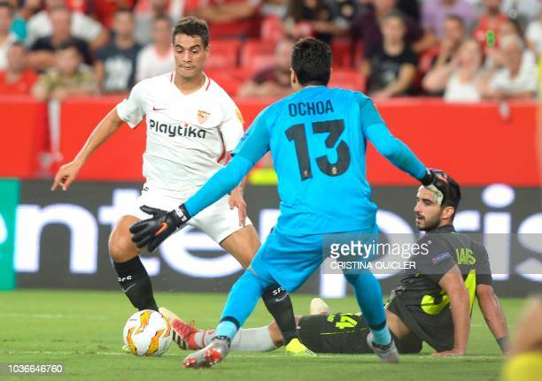 Sevilla's French forward Wissam Ben Yedder vies with Standard Liege's defender Kostas Laifis and goalkeeper Guillermo Ochoa during the UEFA Europa...