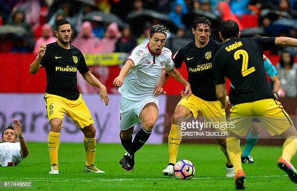 Sevilla's French midfielder Samir Nasri vies with Atletico Madrid's Montenegrin defender Stefan Savic as Atletico Madrid's midfielder Koke looks on...